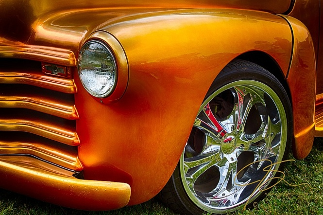 The lovely curves of an old Chevy pickup. Covered in meticulously laid orange paint.