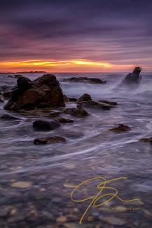 Dramatic eggplant purple skies, with a hint of sunlight breaking through near the horizon. All while the surf crashes over the granite boulders