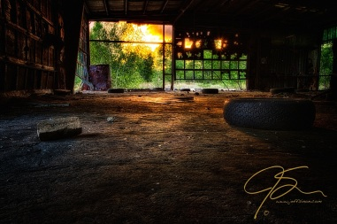 Abandoned garage with sunlight streaming in the broken doors