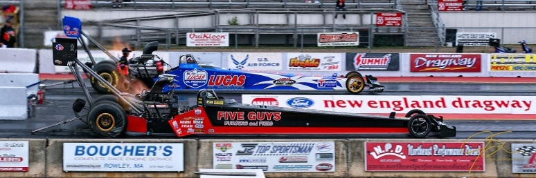 Tire spinning, fire breathing, two top fuel dragsters launch from the starting line at New England Dragway