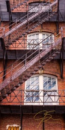 The zigzag of the rusty iron fire escape on an old brick mill building