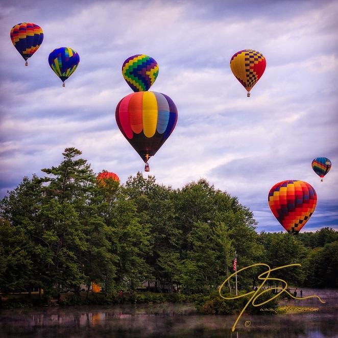 Hot air balloons take flight under cloudy skies.