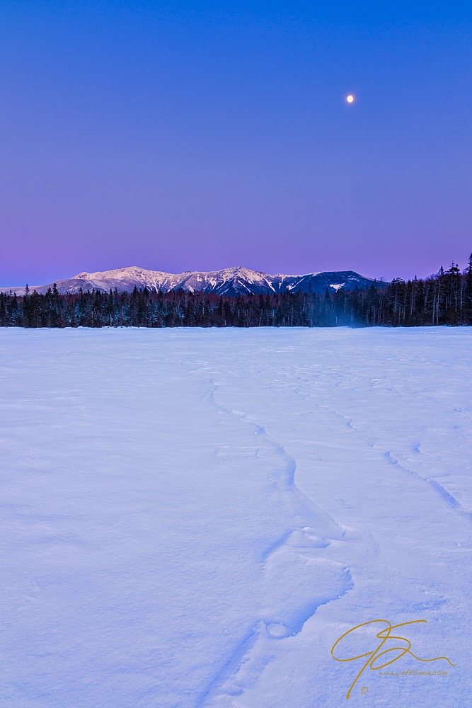 Viewed across the wind swept snow covering Lonesome Lake, late day, blue hour light falling on the snow capped mountains of Franconia Ridge, with the full moon rising high above the mountains.