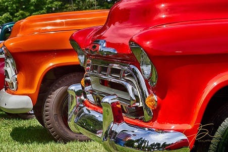Red And Orange, A Pair Of 1957 Chevy Pick-Up Trucks.