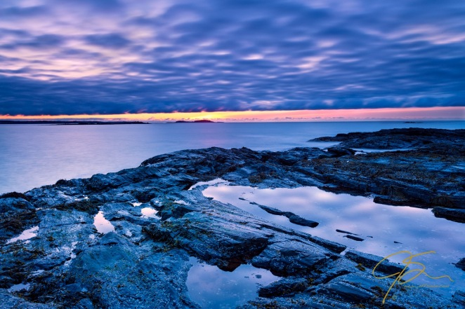 The blue hour over the rocky seacoast along Prouts Neck in Scarborough, Maine