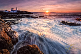 Sunrise over Nubble Light in York, Maine. The sun is just peeking over the clouds on the distant horizon and the rolling surf is crashing over the rocks at my feet.