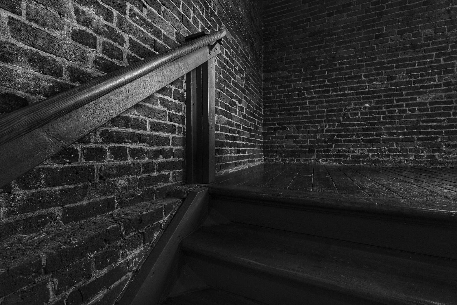 Dark shadowy stairway in an old brick mill building.