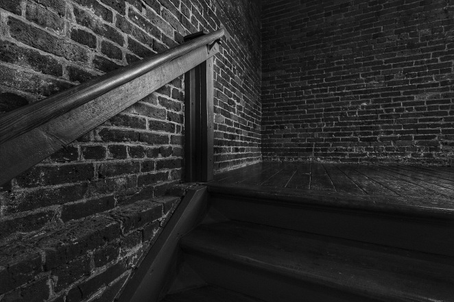 Dark shadowy stairway in an old brick mill building.