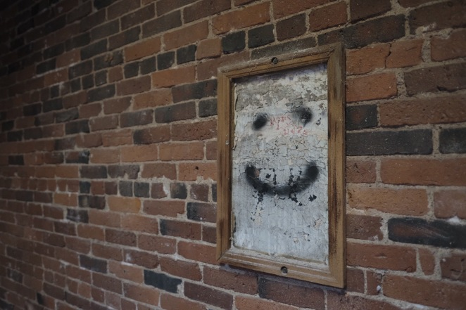 Smiley face graffiti in wooden frame on a brick wall