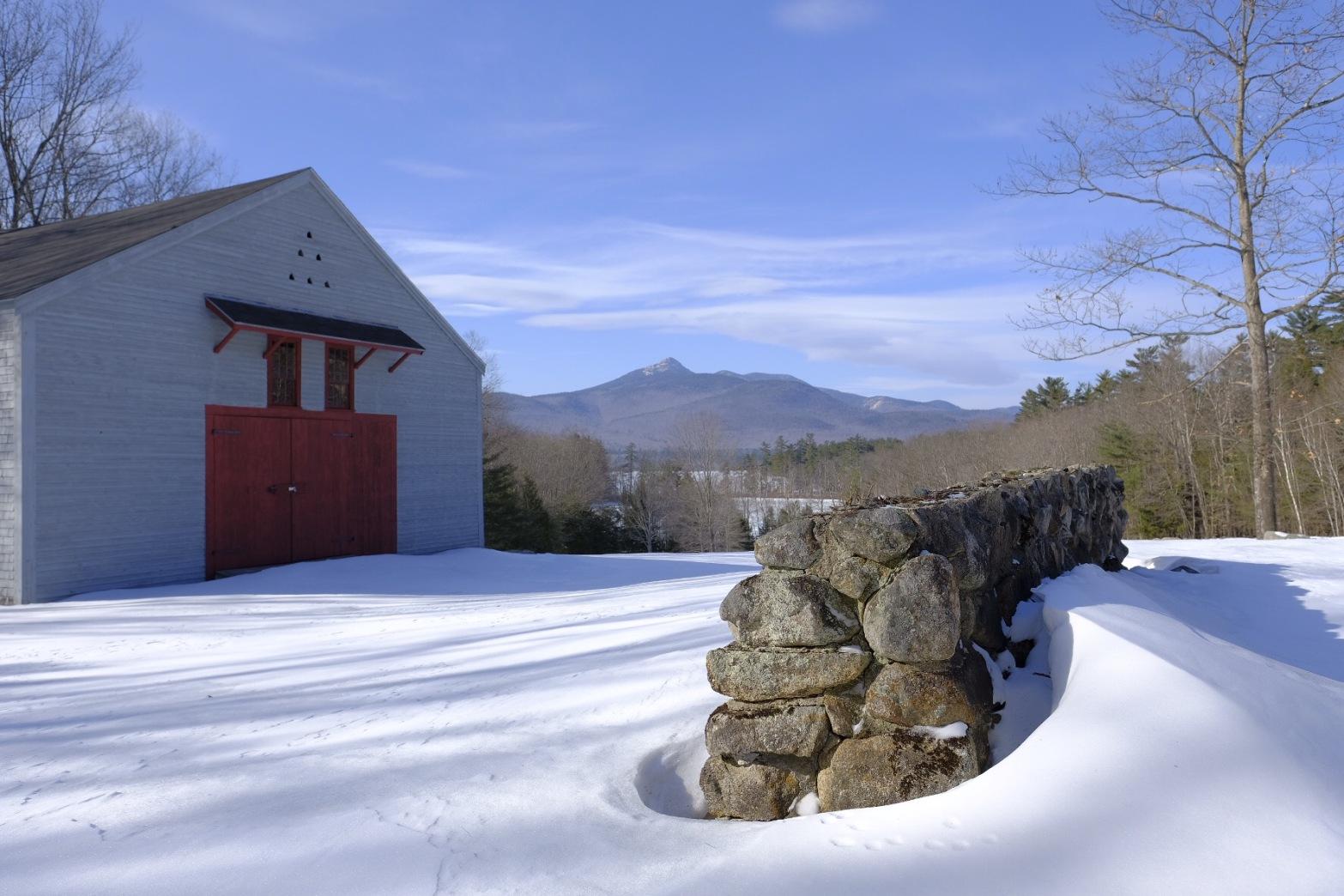 Gray barn with red door, overlooking mount Chocorua, New Hampshire winter scenery