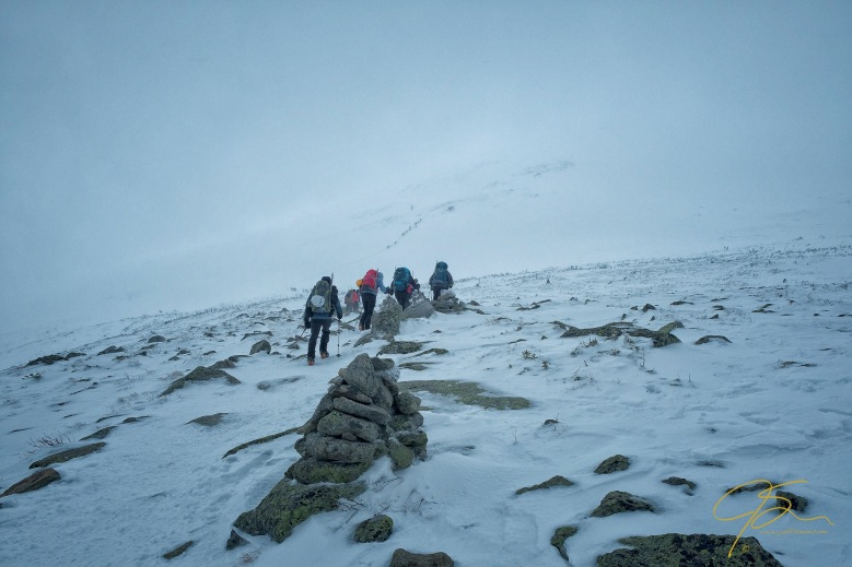 hikers in near whiteout conditions on mount washington.