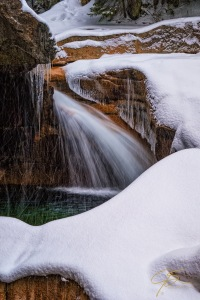 Delicate icicles and a blanket of fresh snow decorate The Basin in Franconia Notch State Park.