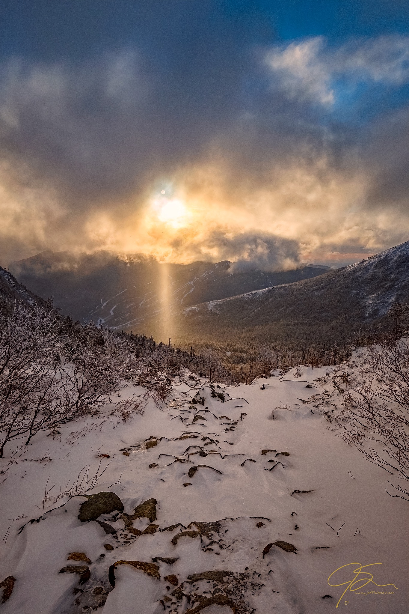 a ray of sunlight beams from the clouds over the base of Tuckerman Ravine and the Hermit Lake shelter.