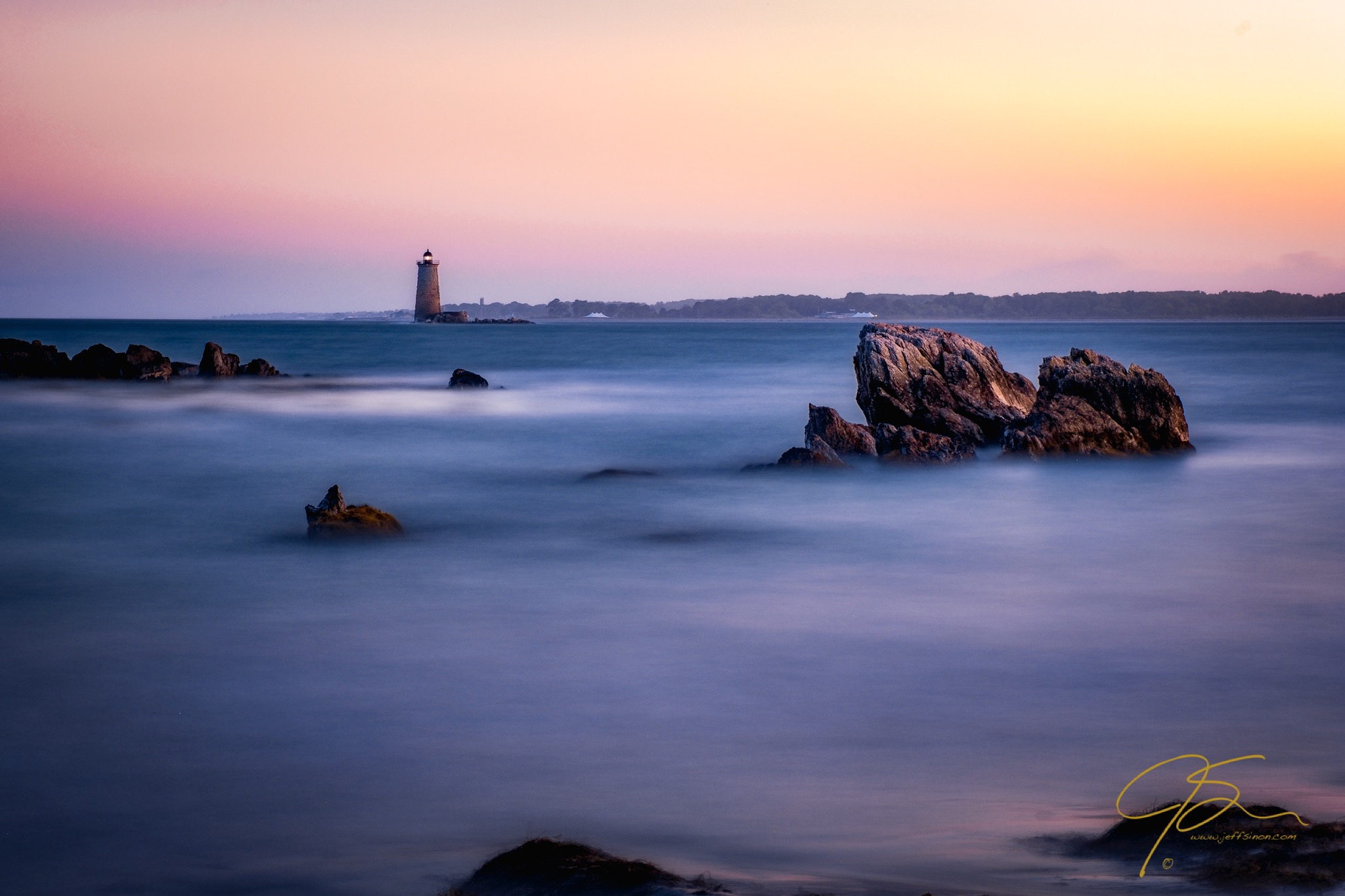 whaleback light at dusk with large rocks in the foreground