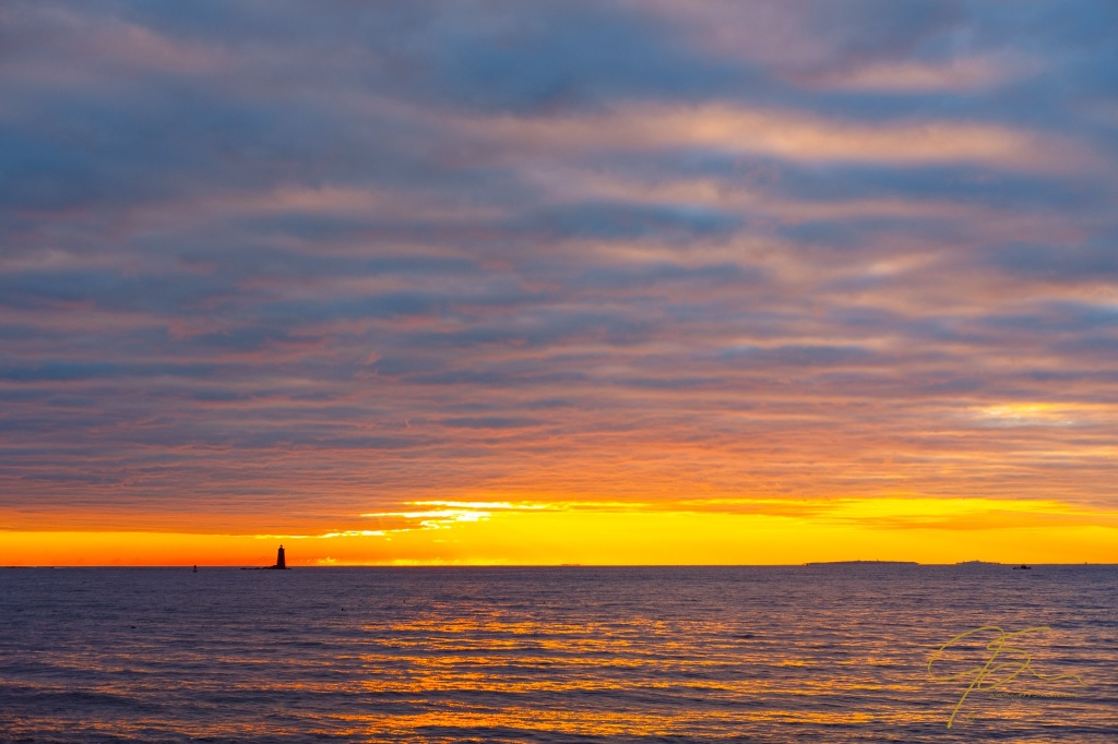 Sunrise off the NH seacoast with Whaleback Lighthouse on the horizon.