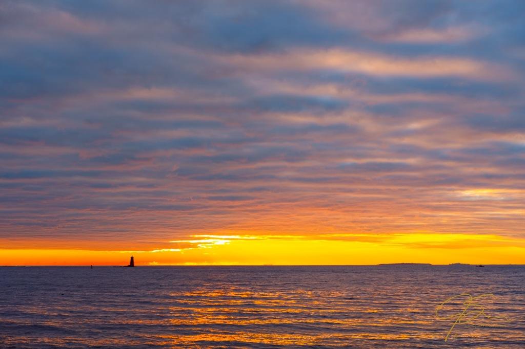 Sunrise off the NH seacoast with Whaleback Lighthouse on the horizon.