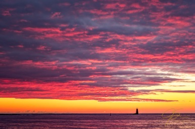 fiery sunrise over whaleback lighthouse