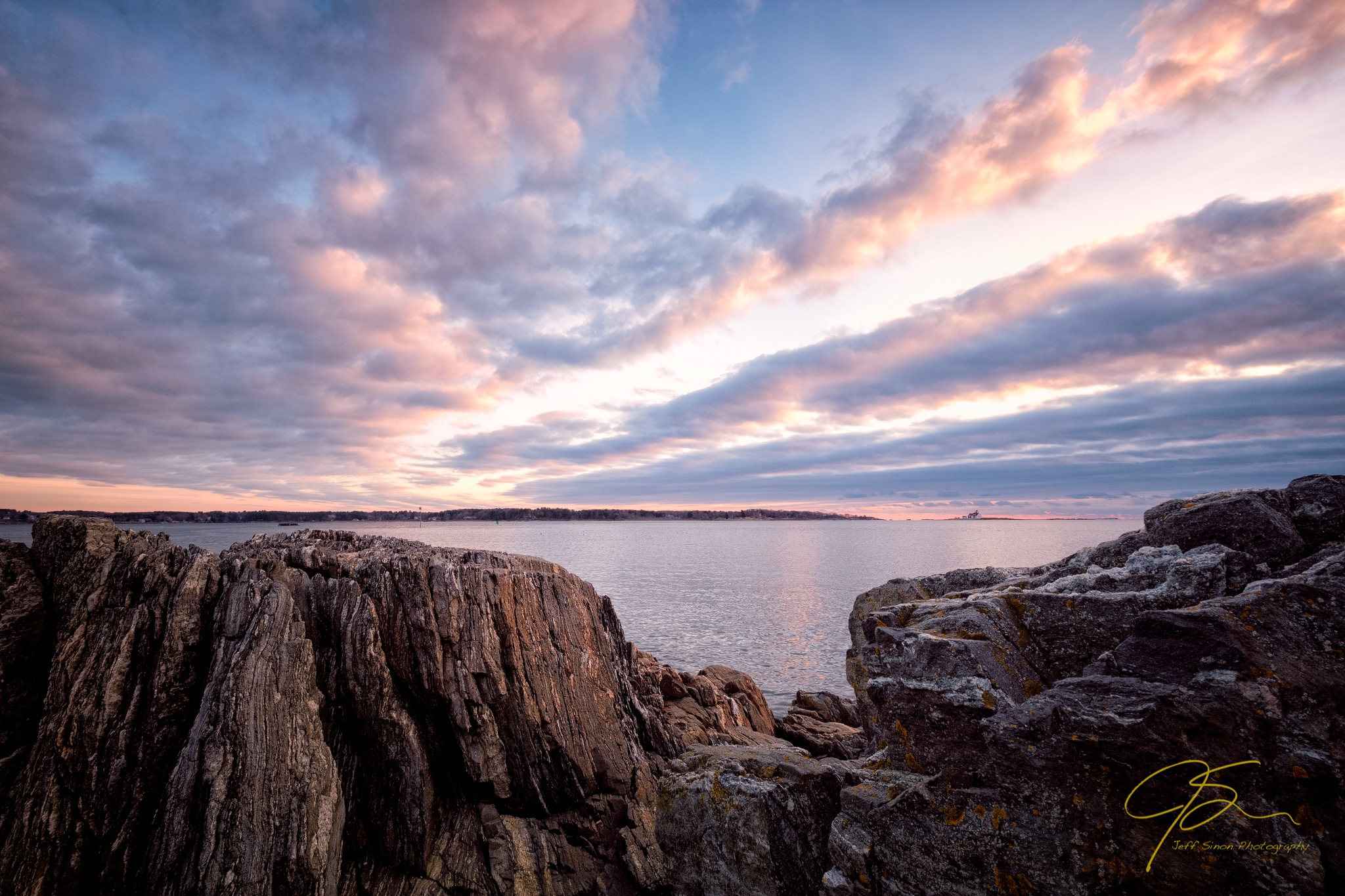 early light and dramatic clouds over the rocky shore of the New Hampshire seacoast