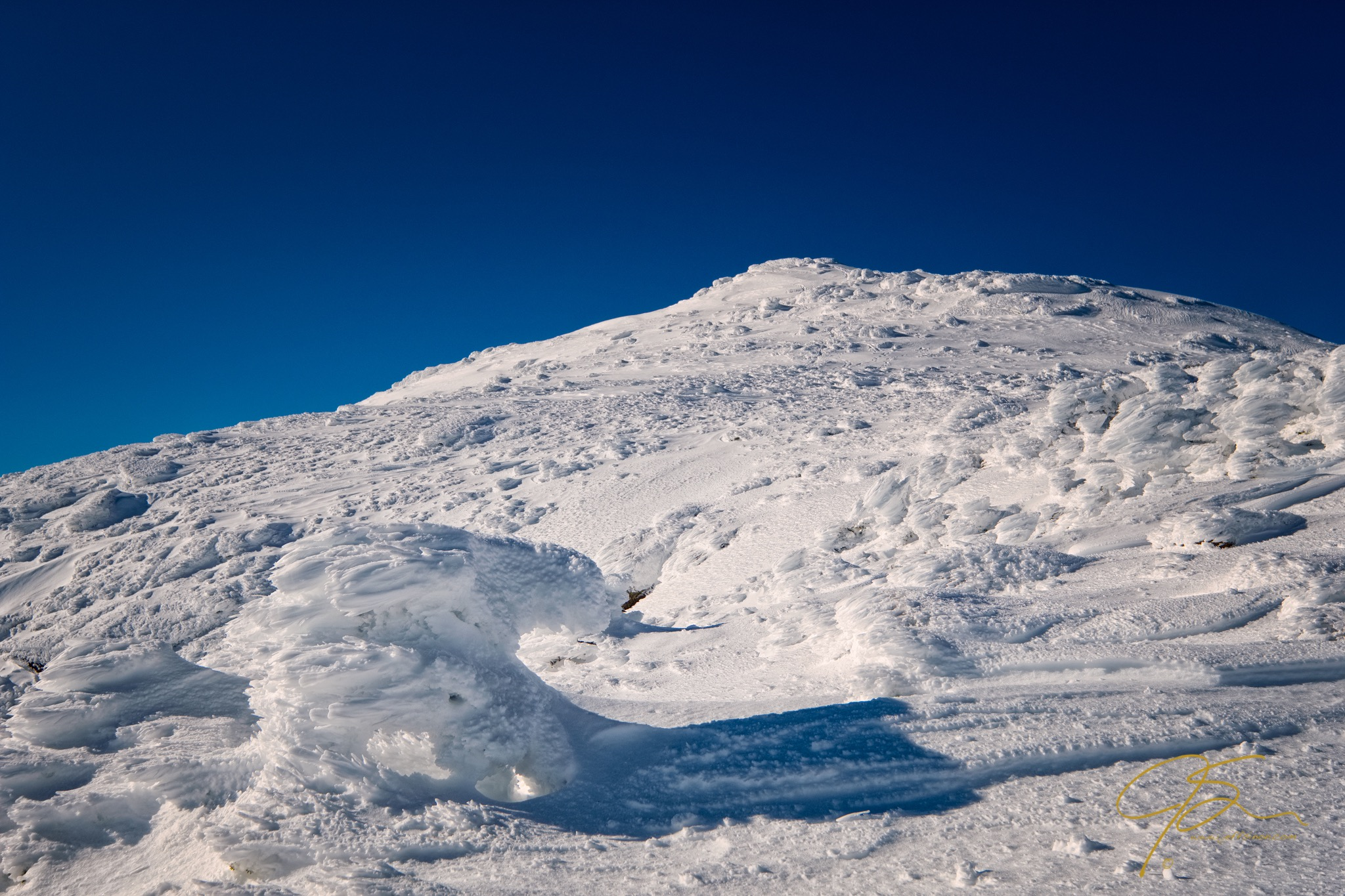 covered in snow and rime ice, New Hampshire's Mount Lafayette is a brilliant white under a clear blue winter sky.
