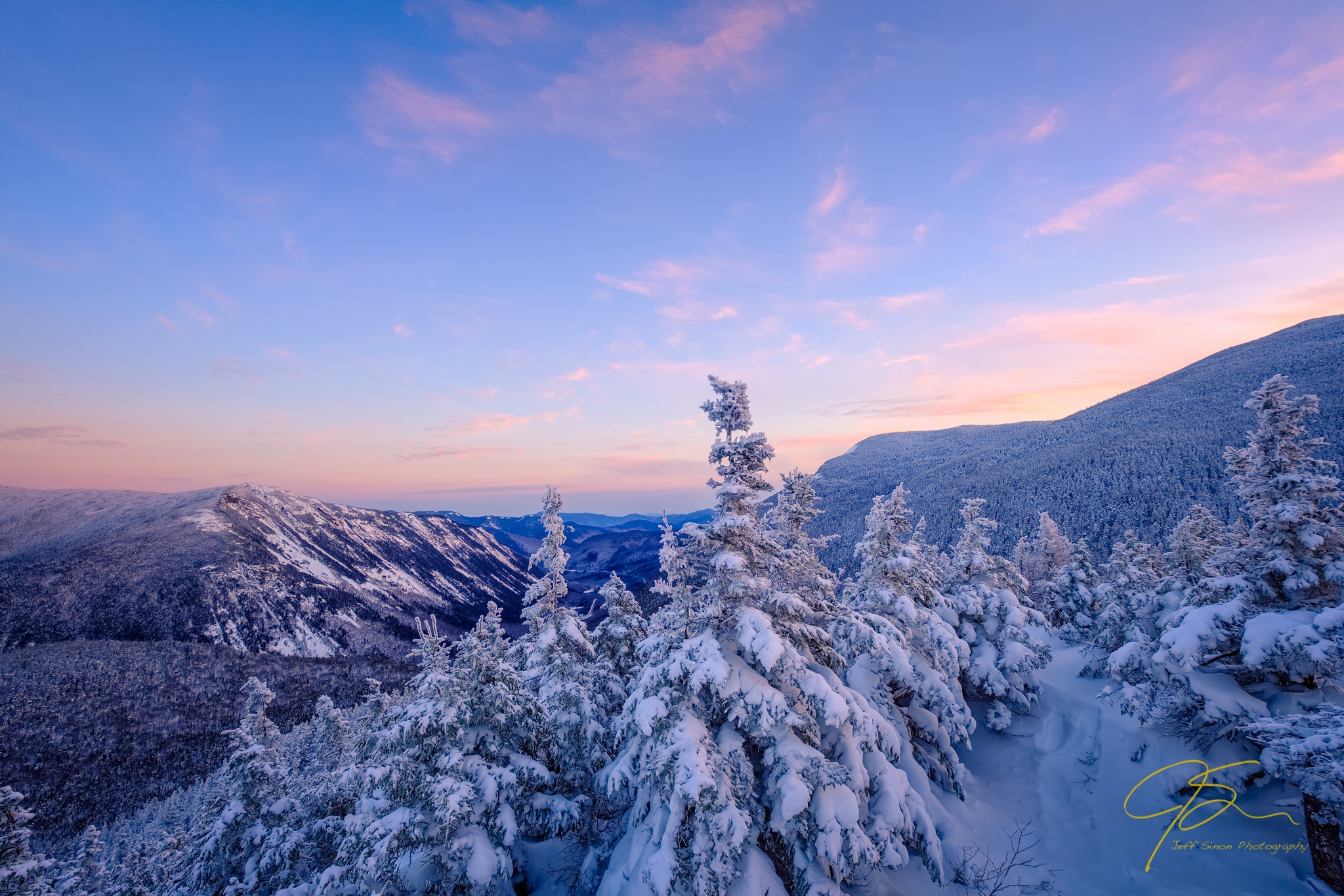 Soft winter light looking down through New Hampshire's Crawford Notch from the snowy summit of Mt. Avalon.