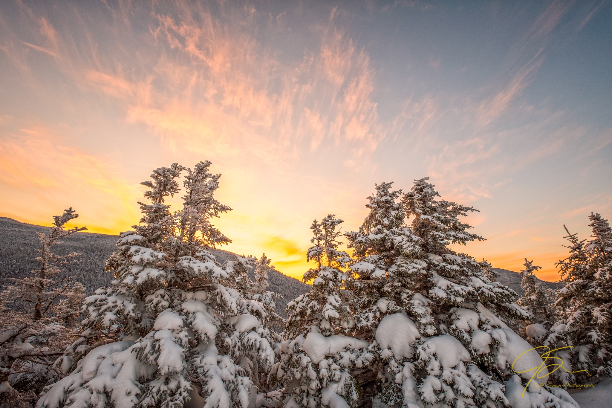 The last of the suns golden glow as it sets over the snowy White Mountains of New Hampshire. The snow covered spruce trees the only witness to the passing of another winter day.