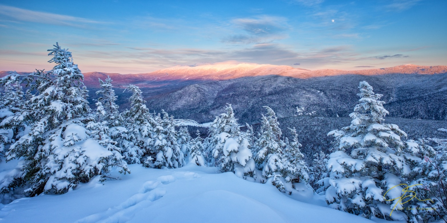 A snowy winter view from the summit of New Hampshire's Mount Avalon. In the distance the majestic snow covered summits of Mount Washington and the Presidential Range are bathed in the warm light of the setting sun.