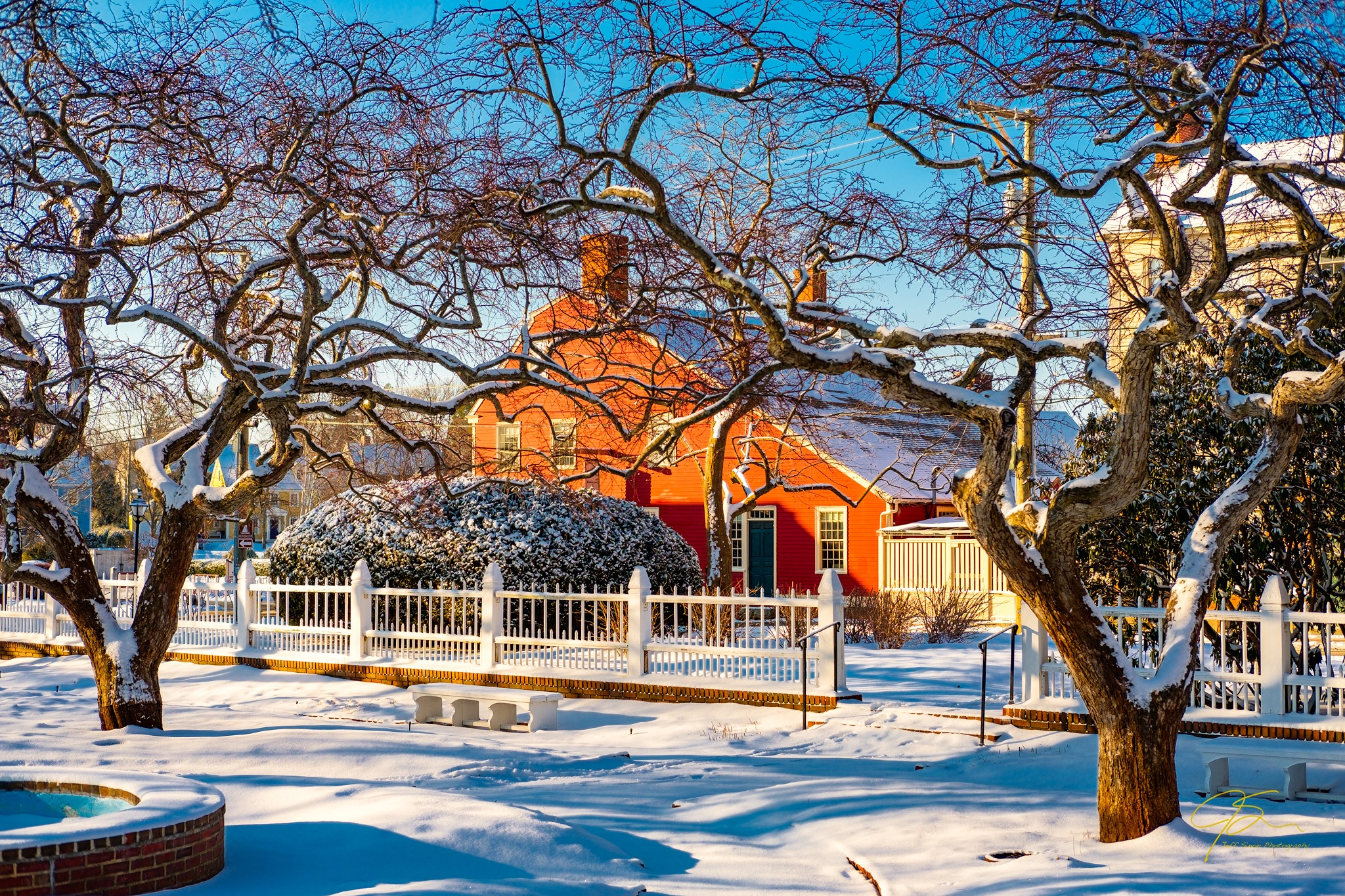 viewing through the Prescott Park gardens after a fresh blanket of snow has fallen. The gnarled crab apple trees frame the red saltbox style house across the street from the garden.