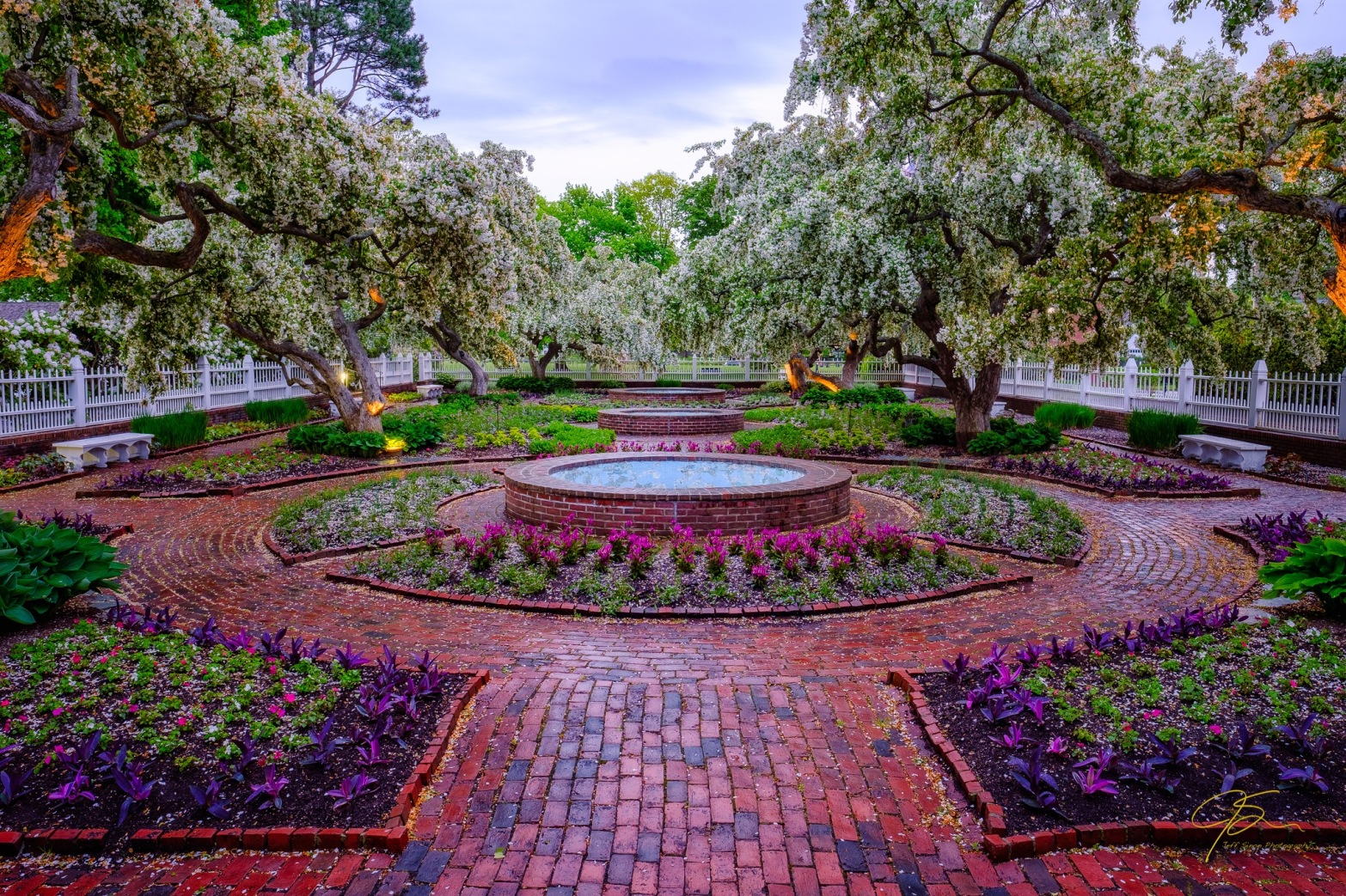 the beautiful gardens in prescott park, brick pathways, circular fountains, and flowers in the beds,