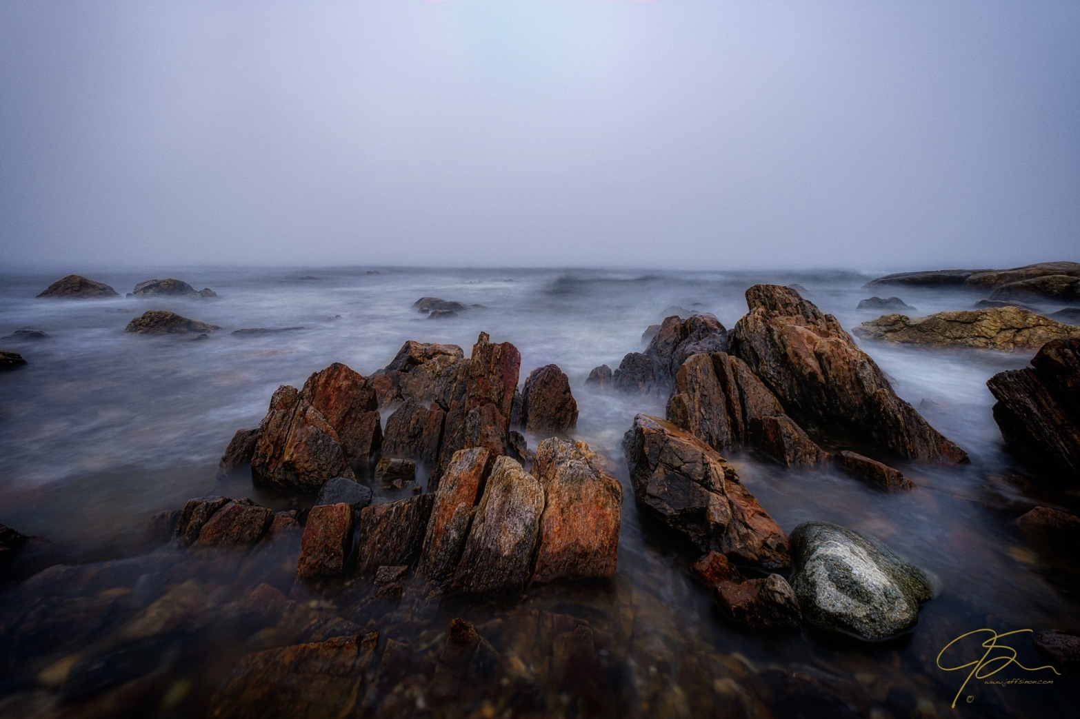 Thick fog along the rocky New Hampshire seacoast, large reddish rocks jut above the incoming tide.