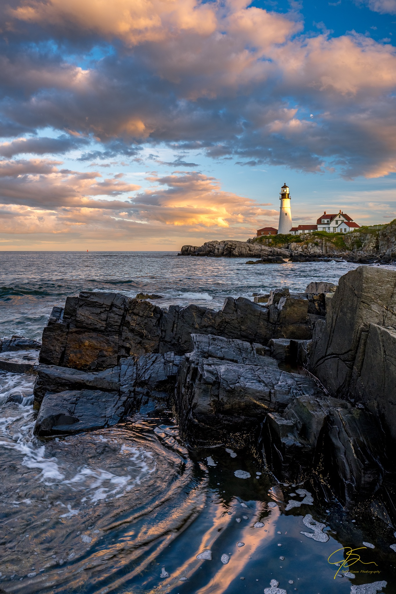 Portland head light with a dramatic sunset sky and rocky foreground