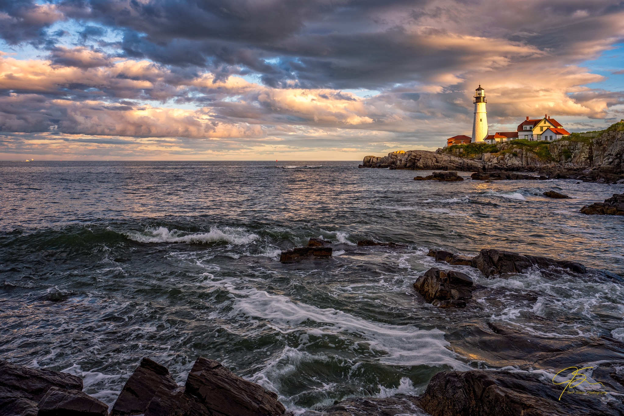 dramatic sky over Portland head light at sunset