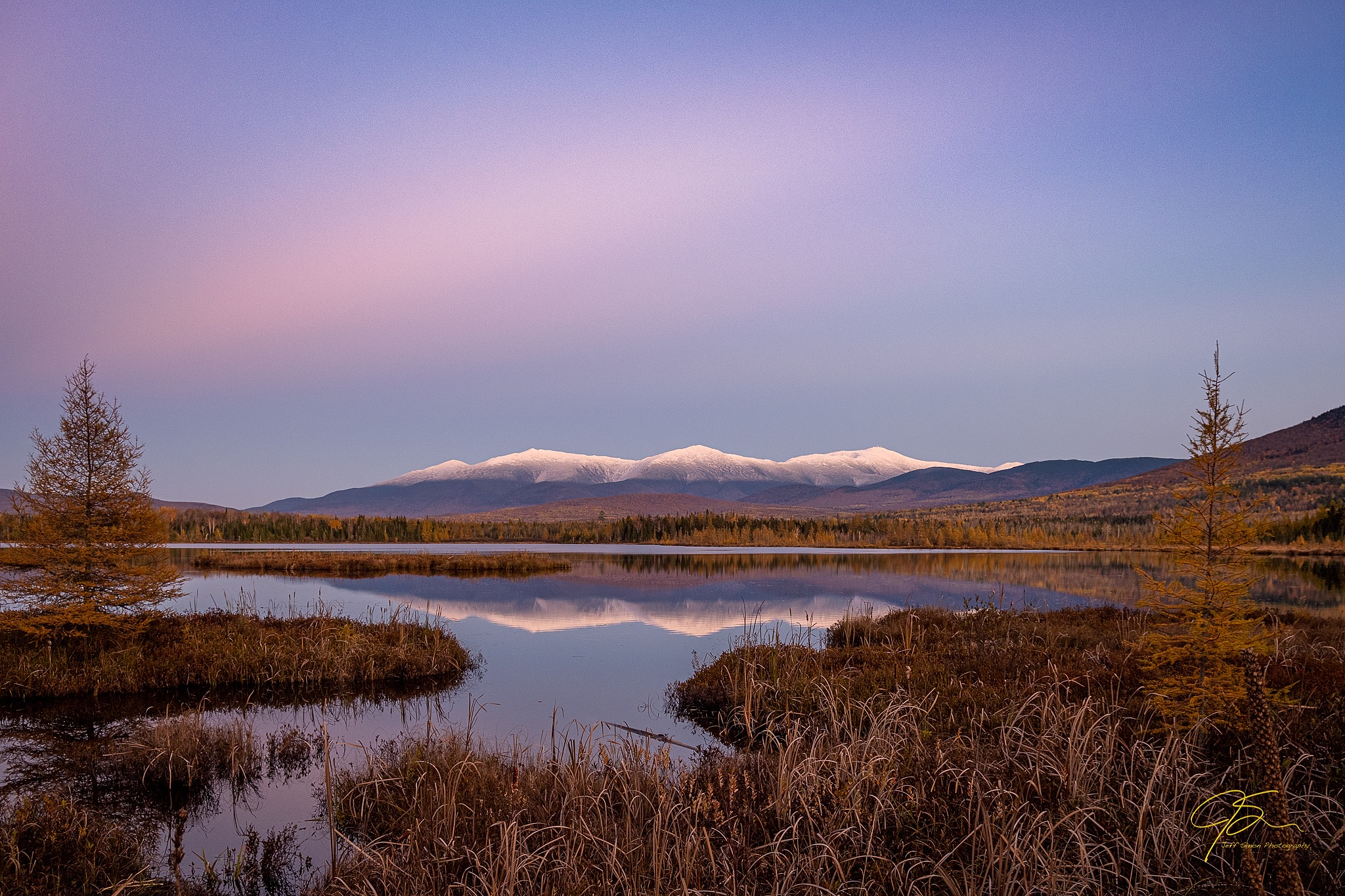 snow capped presidential range reflecting on the surface of cherry pond, white filed, New Hampshire.
