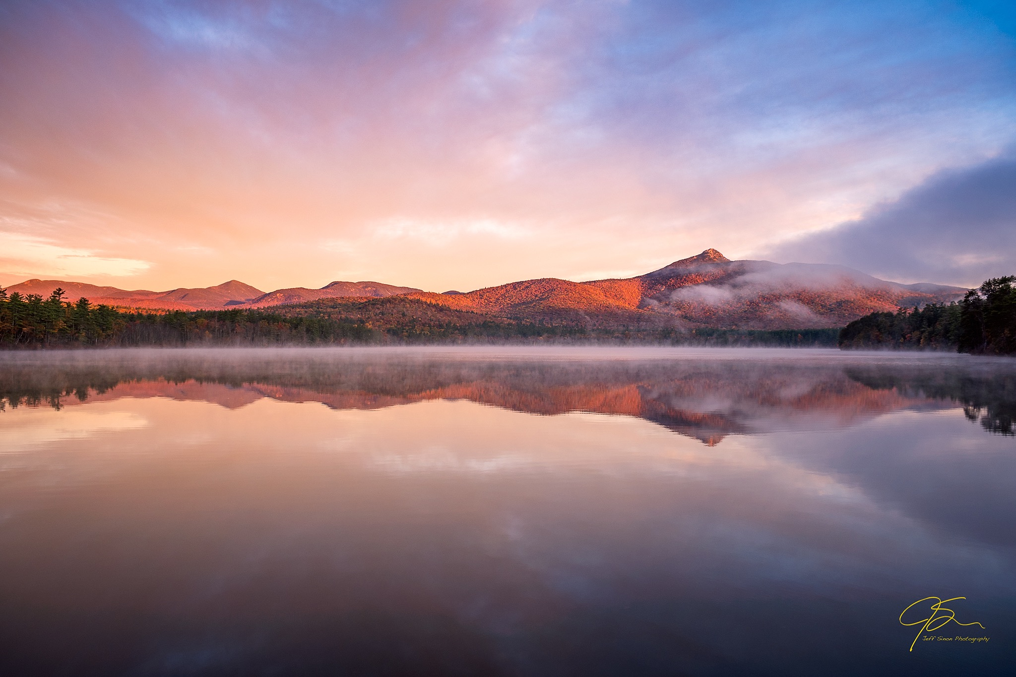 sunrise light illuminates the iconic profile of Mount Chocorua. The mountains summit peeking our from the morning mist, all reflected on the glassy surface of Chocorua Lake.