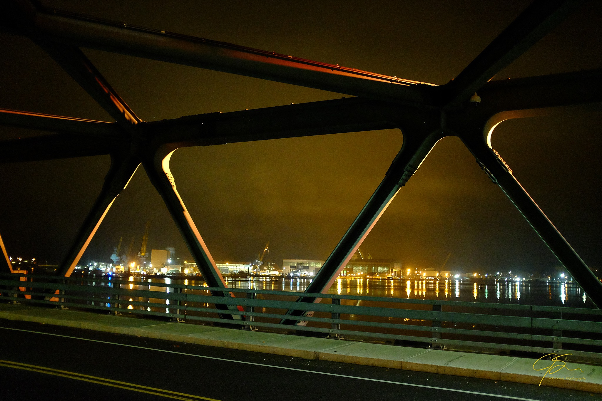 looking through the structure of the memorial bridge towards the portsmouth naval shipyard in Kittery, Maine.