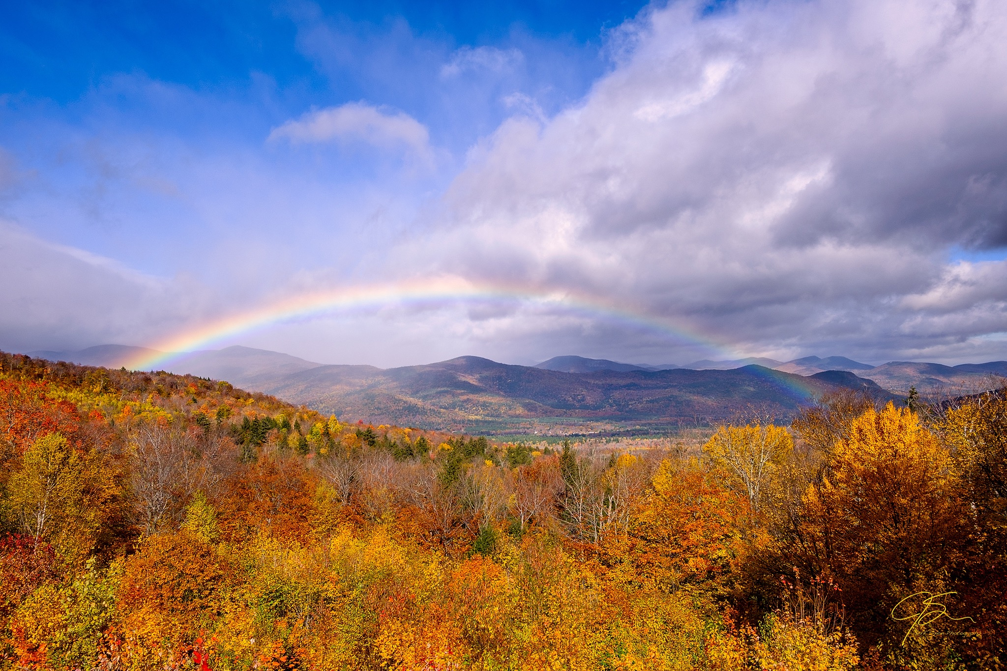 A full rainbow arcs across the sky over the brilliantly colored White Mountains.