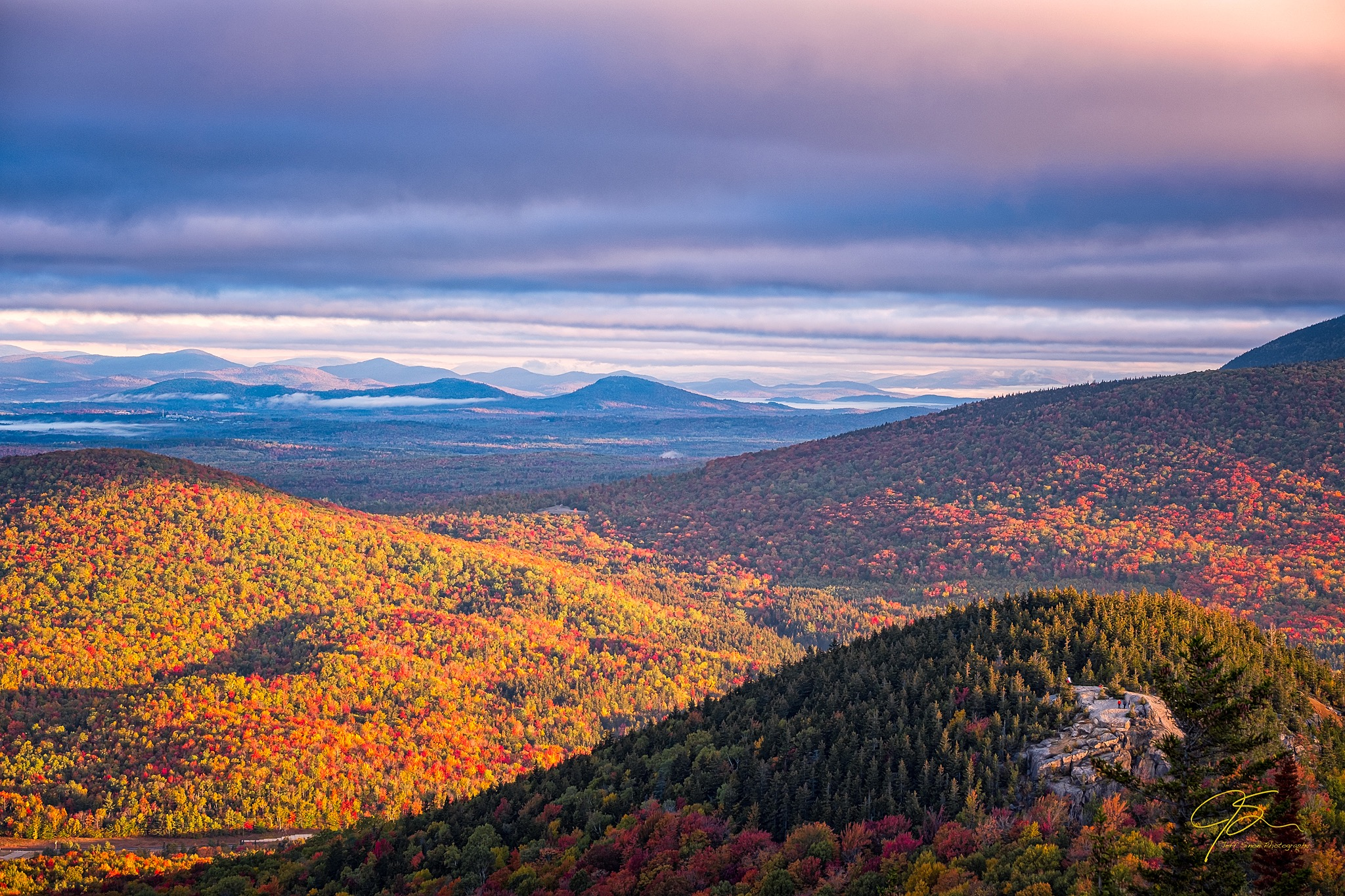 Looking north from the summit of New Hampshire's Middle Sugarloaf Mountain, expansive mountain views stretch toward the horizon. The partially exposed summit of North Sugarloaf can be seen in the lower right corner of the image.