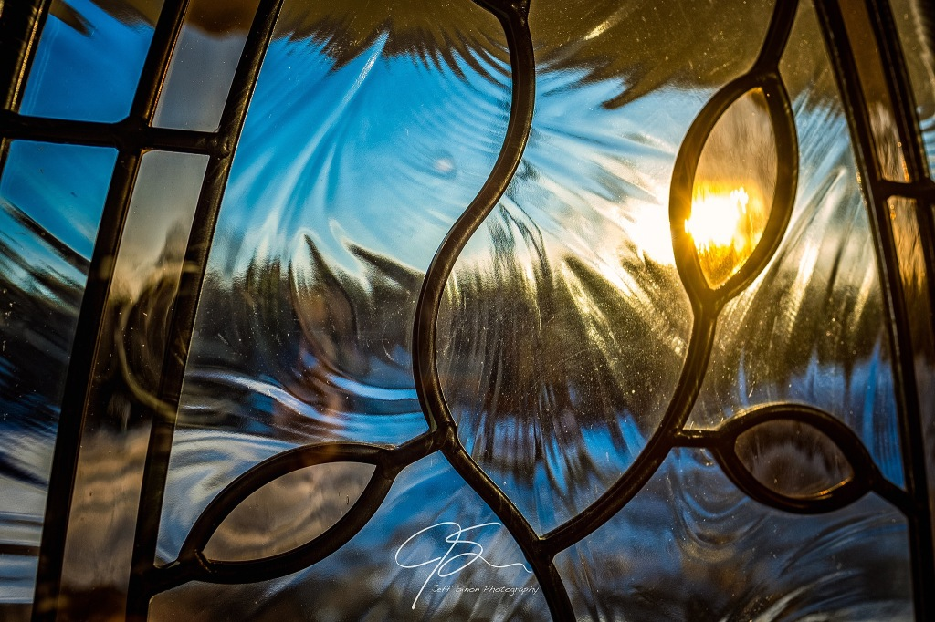 sunlight through a textured stained glass front door window.